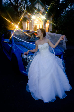 Night wedding photo of bride with ford xr6 blue car outside bram leigh chapel